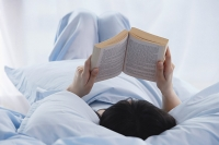 Young woman reading a book in bed - Asia Images Group