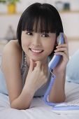 Young woman using telephone, smiling - Asia Images Group