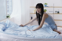 Young woman making her bed - Asia Images Group