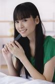 Young woman filing nails, looking at camera - Asia Images Group