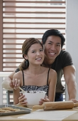 Couple in kitchen, smiling at camera - Asia Images Group