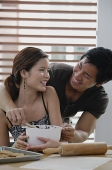 Couple in kitchen, smiling at each other - Asia Images Group
