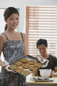 Woman holding baking tray of cookies, man in the background - Asia Images Group