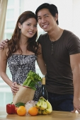 Couple smiling at camera, fresh fruits and vegetables on table in front of them - Asia Images Group