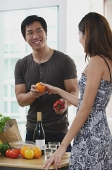 Couple at home, woman passing man a fruit - Asia Images Group