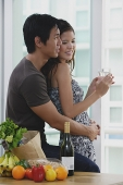 Couple at home, man embracing woman from behind - Asia Images Group