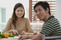 Couple looking at camera, woman chopping vegetables - Asia Images Group