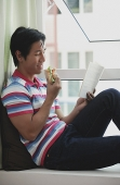 Man sitting on bay window, reading a book, eating a sandwich - Asia Images Group