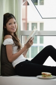 Woman sitting on bay window holding a book, smiling at camera - Asia Images Group