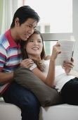 Couple at home, woman leaning on man, reading a book - Asia Images Group