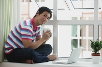 Man sitting on bay window using laptop - Asia Images Group