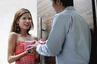 Couple standing at doorway, man giving woman a present - Asia Images Group
