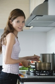 Woman cooking in kitchen, looking at camera - Asia Images Group