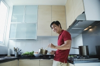 Man cooking in kitchen, smiling at camera - Asia Images Group