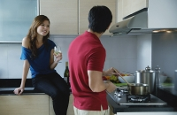 Man cooking in kitchen, looking at woman sitting on kitchen counter - Asia Images Group
