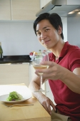 Man sitting down for a meal, raising wine glass toward camera - Asia Images Group