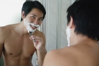 Man shaving, looking at camera through mirror reflection - Asia Images Group