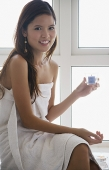 Woman sitting on window ledge, wrapped in a towel, holding candle - Asia Images Group