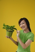 Young Woman with houseplant, smiling at camera - Asia Images Group