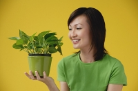 Young Woman looking at plant - Asia Images Group