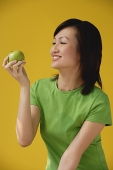 Young Woman looking at apple - Asia Images Group