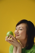 Young Woman holding apple, eyes closed - Asia Images Group