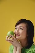 Young Woman holding apple, smiling at camera - Asia Images Group