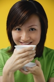 Young woman drinking from tea cup, smiling at camera - Asia Images Group