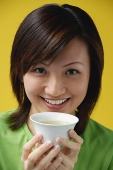 Young woman holding Chinese tea cup, smiling at camera - Asia Images Group