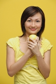 Young woman holding lemon, standing against yellow background - Asia Images Group