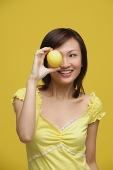 Young woman holding lemon over her eye - Asia Images Group