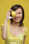 Young woman holding lemon over her eye, portrait - Asia Images Group