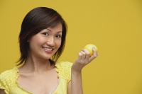 Young woman holding lemon, smiling - Asia Images Group
