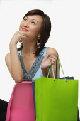Young woman with shopping bags, looking away, hand on chin - Asia Images Group