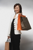 Young woman with shopping bags, smiling - Asia Images Group