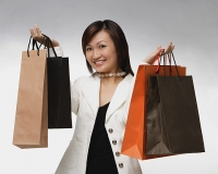 Young woman carrying shopping bags, smiling - Asia Images Group