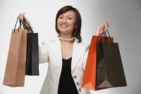 Woman carrying shopping bags, smiling , portrait - Asia Images Group