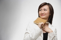 Young woman holding purse, looking away - Asia Images Group