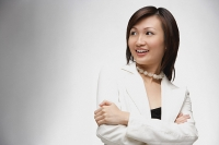Young businesswoman, arms crossed, looking away, smiling - Asia Images Group