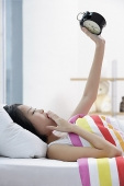 Young woman lying on bed, looking at alarm clock, hand on mouth - Asia Images Group