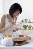 Young woman sitting on bed, having breakfast - Asia Images Group