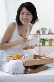 Young woman having breakfast in bed - Asia Images Group