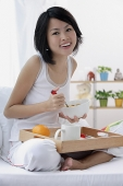 Young woman having breakfast in bed, smiling at camera - Asia Images Group