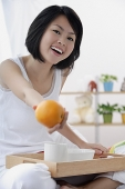 Young woman holding orange towards camera, smiling - Asia Images Group