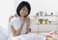 Young woman sitting on bed, hugging pillow - Asia Images Group