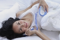 Young woman lying on bed, using telephone, smiling at camera - Asia Images Group