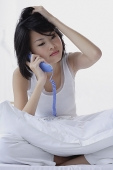 Young woman using telephone, hand on head - Asia Images Group
