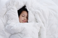 Young woman sleeping, covered by blanket - Asia Images Group