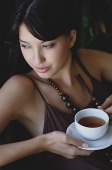 Young woman holding cup and saucer - Asia Images Group