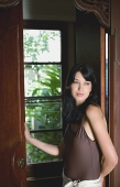 Young woman leaning on door frame, looking away - Asia Images Group